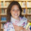 Close-up of a smiling female student in the library — Stock Photo