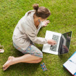 Female student using laptop with books at the park — Stock Photo #36172463