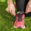 Stock Photo: Close up of sporty womtying her shoelaces