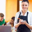 Waitress writing an order with students using laptop at coffee — Stock Photo