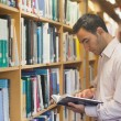 Stock Photo: Intellectual mreading book standing in library
