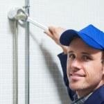 Cheerful plumber repairing shower head — Stock Photo #36173039