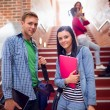 Couple with students behind on stairs in the college — Stock Photo