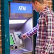 Stock Photo: Handsome student withdrawing cash