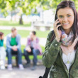 College girl using mobile phone with blurred students in park — Stock Photo
