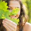 Gorgeous smiling brunette holding a leaf — Stock Photo