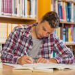 Stock Photo: Handsome concentrated student studying his books