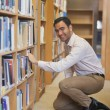 Young attractive mcowering in front of bookshelves — Stock Photo #36174441