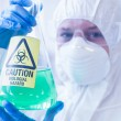 Scientist in protective suit with hazardous chemical in flask — Stock Photo #36174509