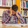 Handsome frustrated student studying his books — Stock Photo #36174709