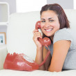 Amused young woman using a red dial phone — Stock Photo #36174723