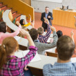 Stock Photo: Students raising hands with teacher in lecture hall