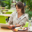 Woman using tablet PC in the cafeteria — Stock Photo #36174881