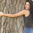Stock Photo: Casual attractive brunette embracing tree looking at camera