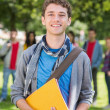 College boy holding books with students in park — Stock Photo