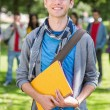 Stock Photo: College boy holding books with blurred students in park