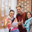 Three smiling students standing next to notice board showing thu — Stock Photo #36175091