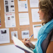 Casual student taking notes in front of notice board — Stock Photo