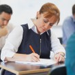 Stock Photo: Concentrated female mature student sitting in classroom