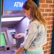 Stock Photo: Pretty brunette student withdrawing cash