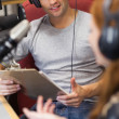 Stock Photo: Attractive radio host interviewing guest holding clipboard