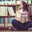 Thoughtful female student against bookshelf on the library floor — Stock Photo #36175579