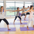 Full length of sporty people stretching hands at yoga class — Stock Photo #36175645