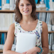 Smiling female student against bookshelf in library — Stock Photo