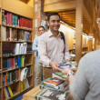 Stock Photo: Mature female librarihanding book to young man