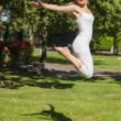 Side view of young cheerful woman jumping spreading her arms — Стоковое фото