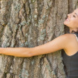 Stock Photo: Casual content brunette embracing tree with closed eyes