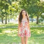 Stylish day dreaming brunette walking on grass — Stock Photo #36176297