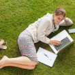 Female student using laptop with books at the park — Stock Photo