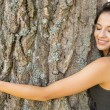 Stock Photo: Casual gorgeous brunette embracing tree with closed eyes