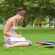Stock Photo: Female student doing homework at the park
