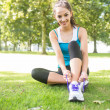 Stock Photo: Smiling active brunette tying her shoelaces
