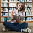 Happy student against bookshelf with tablet PC on the library fl — Foto Stock #36176581