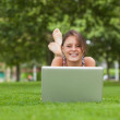 Smiling woman lying on grass and using laptop — Stock Photo