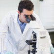 Male scientific researcher using microscope in lab — Stock Photo #36176649