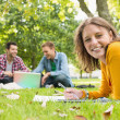 Female writing notes with students using laptop at park — Stock Photo