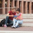 Happy students sitting on stairs using tablet — Stock Photo