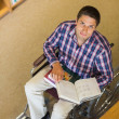 Stock Photo: Portrait of a man in wheelchair reading a book in library