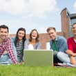 Students with laptop in the lawn against college building — Stock Photo #36176953