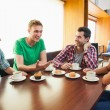 Four casual students having cup of coffee chatting — Stock Photo #36177083