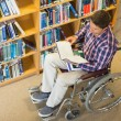 Stock Photo: Man in wheelchair reading a book in the library