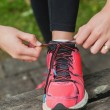 Stock Photo: Close up of young womtying her shoelaces