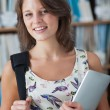 Female student against bookshelf with tablet PC and bag — Stock Photo