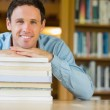 Smiling mature student with stack of books at library desk — Stock Photo #36177379