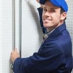 Smiling plumber repairing shower head — Stock Photo #36177405