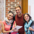 Three smiling students standing next to notice board — Stock Photo #36177431